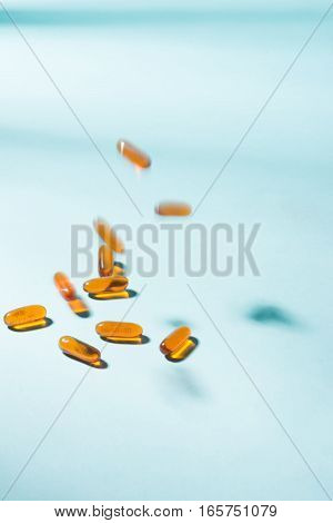 Pills falling down. Gel Capsules. Vitamin A E fish oil primrose oil rice barn oil and other oily drugs.