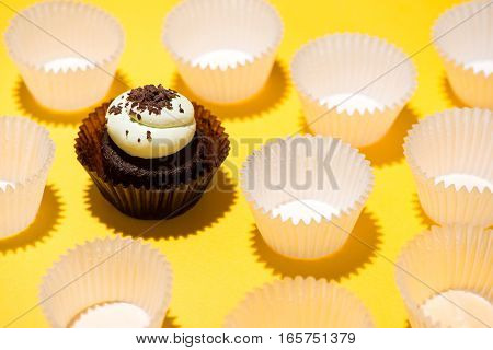 Birthday cup cake against a yellow background