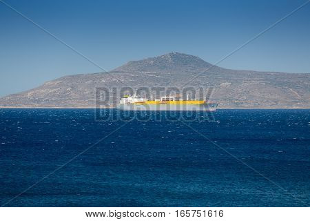 Large cargo ship in the sea against mountains