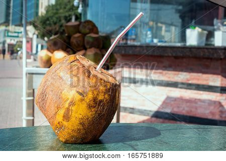 Coconut with a straw to drink on the table. refreshment