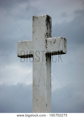 Picture of an old Christian cross standing in front of cloudy sky