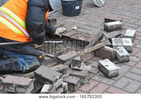 A worker remove and repair concrete paving blocks.