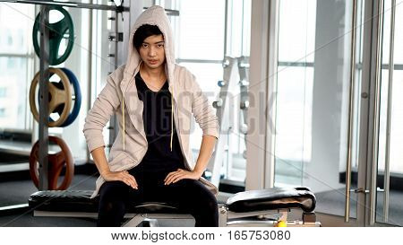 Asian Sportwoman Wearing Hood Resting After Exercise At Gym