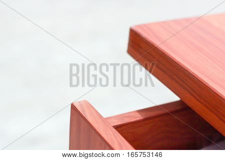 Corner of wood table and drawer on white background
