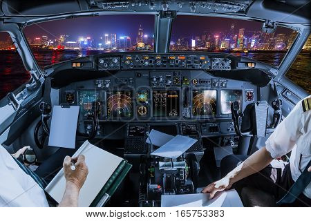 Airplane cockpit flying on Hong Kong panorama skyline with pilots arms and blank white papers for copy space.