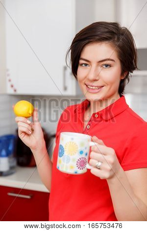 Girl with lemon and cup in hand at kitchen