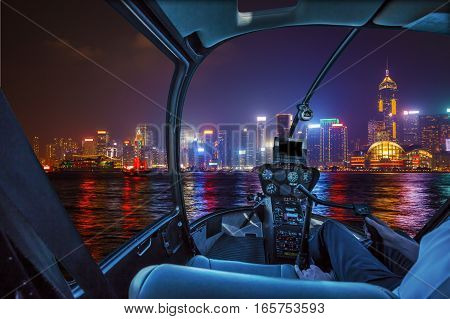 Helicopter cockpit flying on Hong Kong panorama skyline with pilot arm.