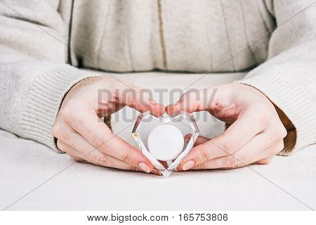 Red heart-shaped crystal lantern in human hands. Concept of Valentine's gift