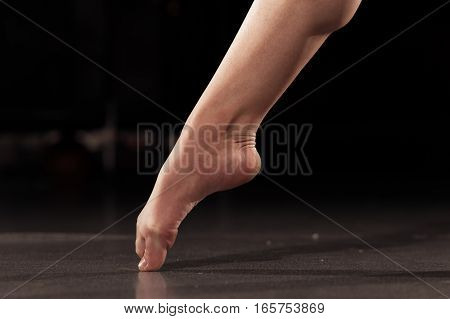 Female teen dancer warming up and stretching legs before doing ballet routine, closeup