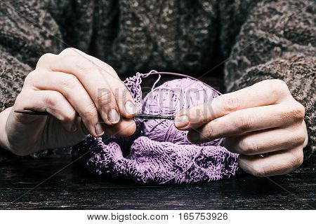 Human hands knitting with round needles on the table