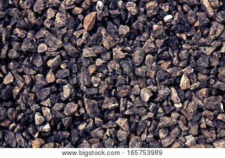 a pile of gravel / grit of glauconite sandstone consisting of gray coarse stones, broken and crushed at a stonepit to similar sizes. The rocks in this aggregate have irregular shapes and a dark color tone.