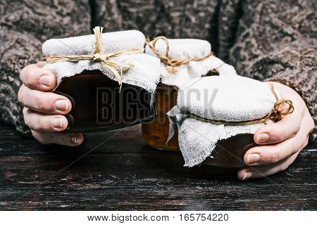 Human hands holding various glass cans of honey