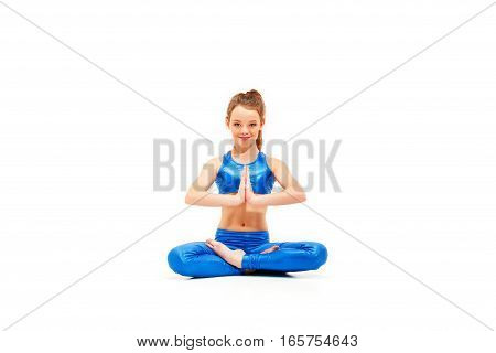 Studio shot of a young fit girl doing yoga exercises on white studio background