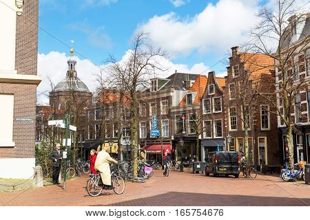 Leiden, Netherlands - April 7, 2016: Traditional houses, Street view and people riding bicycles in Leiden, Holland, Netherlands