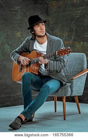 Cool guy with hat playing guitar on gray studio background