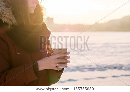 Enjoying hot drink outdoors in winter. Young female person in red parka coat holds paper cup of steaming tea or coffee on a cold sunny winter day