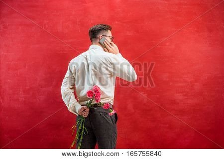 Man with phone holding bouquet of carnations behind back on red studio background