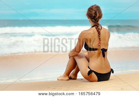 Outdoor summer portrait of young elegant pretty fit woman sitting backwards and looking to the sea at tropical beach. Sports girl enjoy nature paradise and fresh air at wonderful summer vacation.