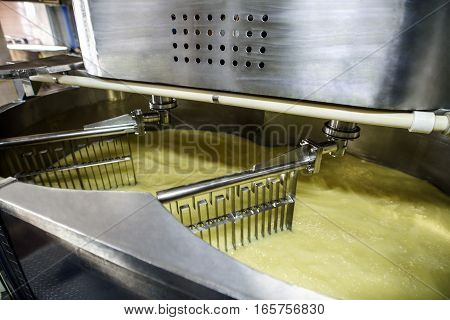 Equipment at dairy processing plant. Automatic tirring machine at cheese production process.