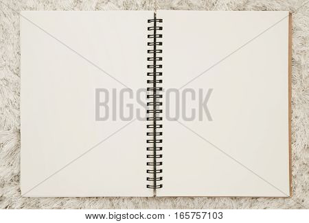 Blank spiral notepad notebook, on white carpet fur texture