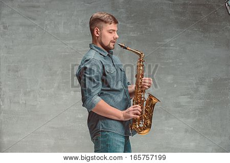 Happy saxophonist with sax on gray studio background