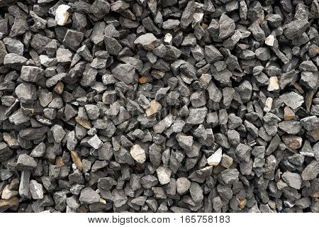 coarse stone gravel - a stack of aggregate with irregular sized, shaped and colored stones. poster
