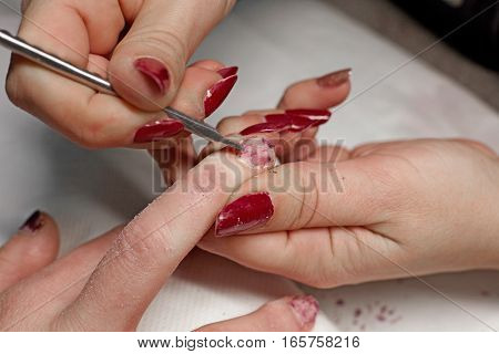 Manicurist removing the polish from the girl client nail at beauty salon.