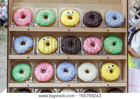Assorted tasty colorful donuts on wooden showcase, close up view. Street food market