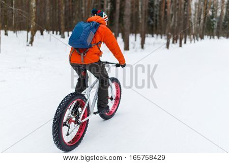 Athlete on bicycle in forest at winter day