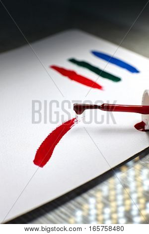 Brush of red nail polish spilled on a white paper.