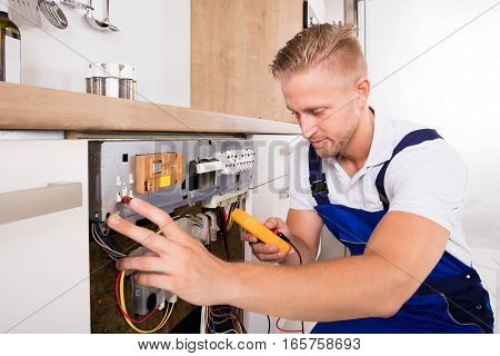 Young Male Technician Fixing Dishwasher With Digital Multimeter