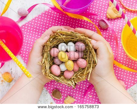 Child holding Easter nest with chocolate candy eggs Easter concept background top view