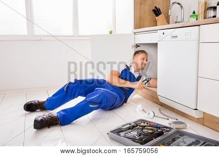 Young Male Plumber Repairing Sink In Kitchen