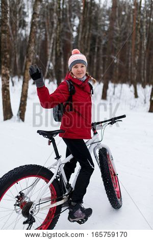 Woman in red jacket on bicycle at winter forest