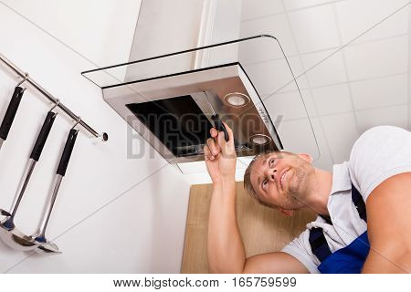 Young Male Technician Checking Kitchen Extractor Filter With Screwdriver