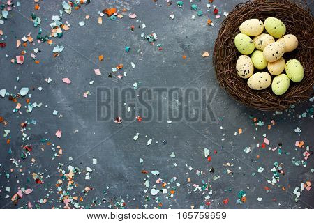 Easter background with Easter nest chocolate candy eggs and eggshell top view