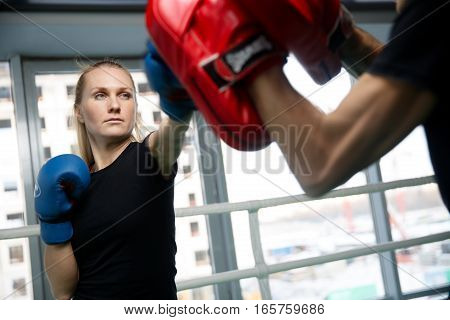Young woman engaged in boxing in gym