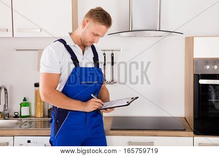 Young Repairman Writing On Clipboard In Kitchen