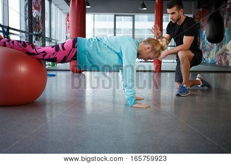 Girl in sportswear is engaged on fitball in gym