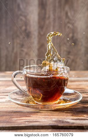Slop out tea in mug on table of glass
