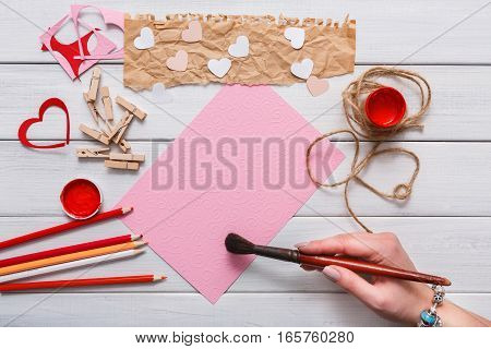 Valentines day, wedding or other holiday decorations background. Handmade gift greeting card creating, painting red hearts, craft paper and diy tools on white wood. Above view, flat lay