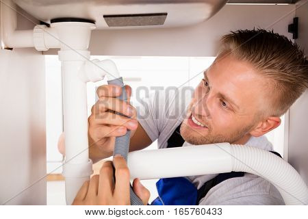 Close-up Of Happy Young Male Plumber Repairing Sink Pipe