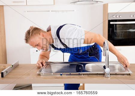 Happy Male Plumber Fixing Stainless Steel Sink In Kitchen