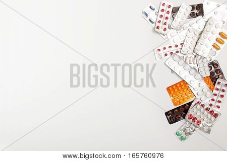 Heap of medicine tablets and pills in blisters on white background. Copy space. Healthcare or medicament addiction concept