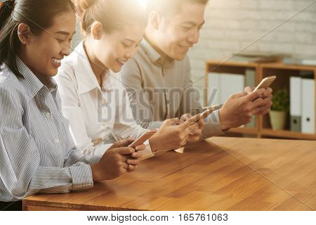 Smiling Asian business people sitting at table and texting