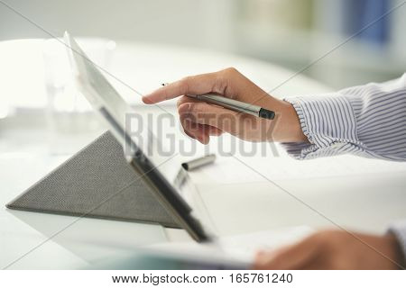 Hand of businessman using tablet computer in work