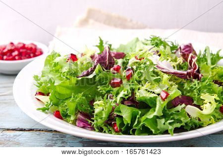Green salad with spinach, frisee, arugula, radicchio and pomegranate seeds on blue wooden background, horizontal