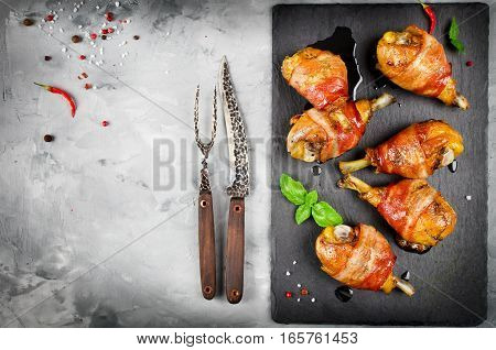 Bacon wrapped chicken legs on a black background. Top view