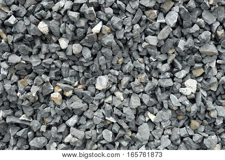 gravel of coarse loose stones - a stack of stone aggregate located at a stonepit. The rocks have irregular shapes from being crushed into similar sizes. Some are light gray or even yellow.