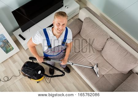 High Angle View Of A Young Man Cleaning Floor With Vacuum Cleaner